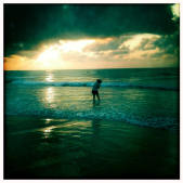 photo of a girl playing in ocean waves as sunrise